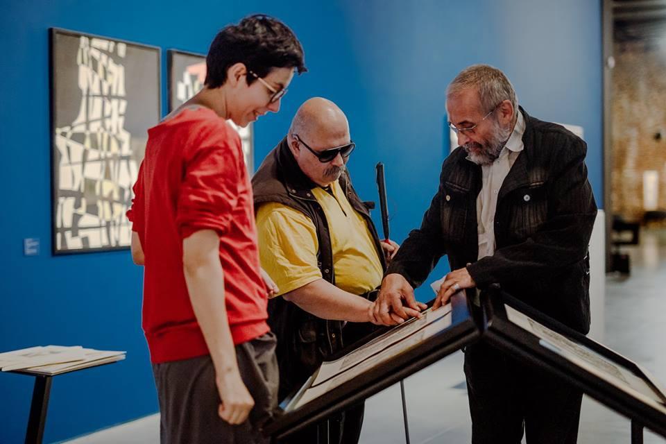 kilka osób na wystawie Marii Jaremy - jedna z nich dotyka tyflografikę, w tle na ścianach abstrakcyjne obrazy