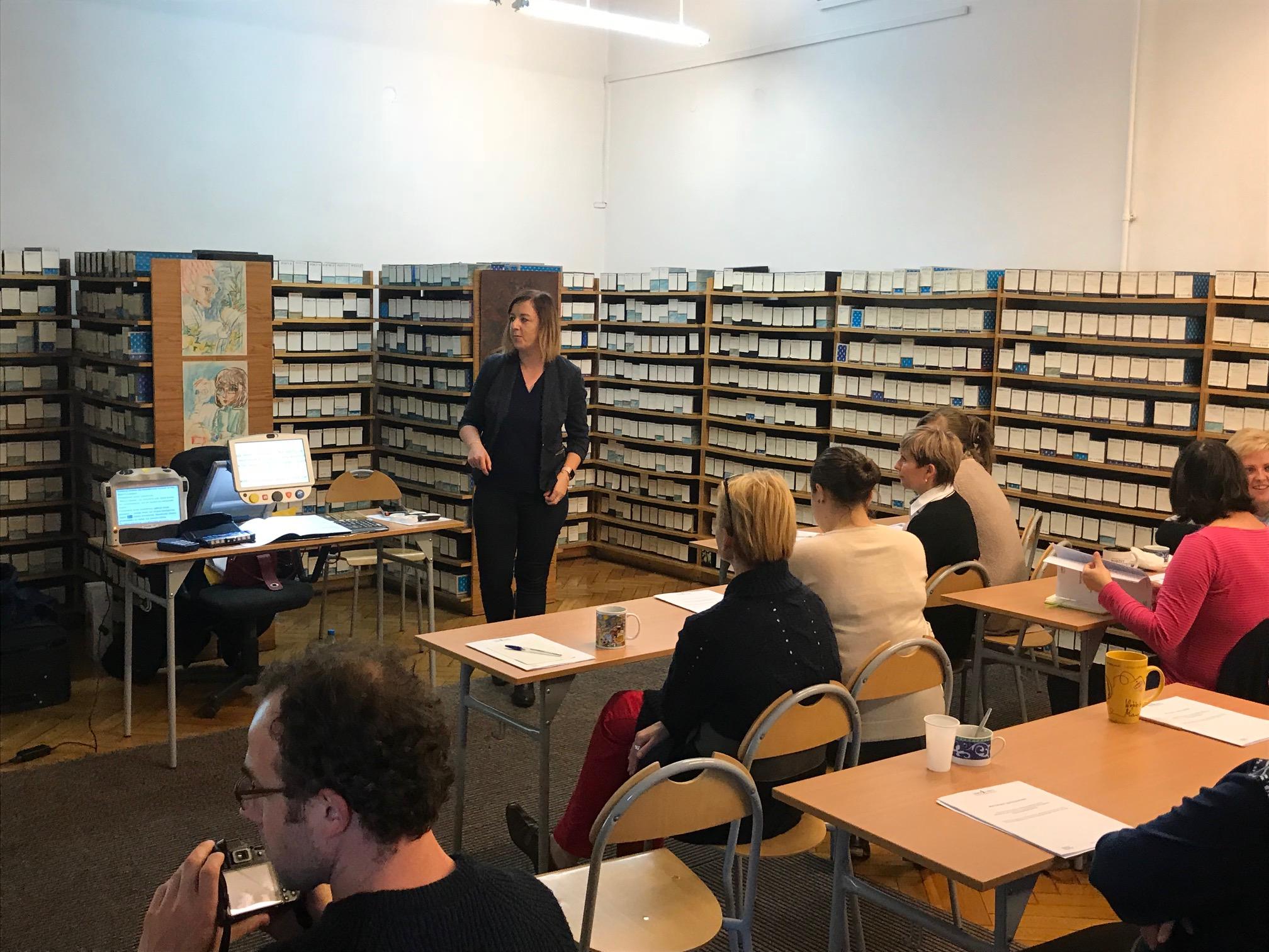 we wnętrzu biblioteki, siedzące osoby słuchają szkolenia o sprzęcie