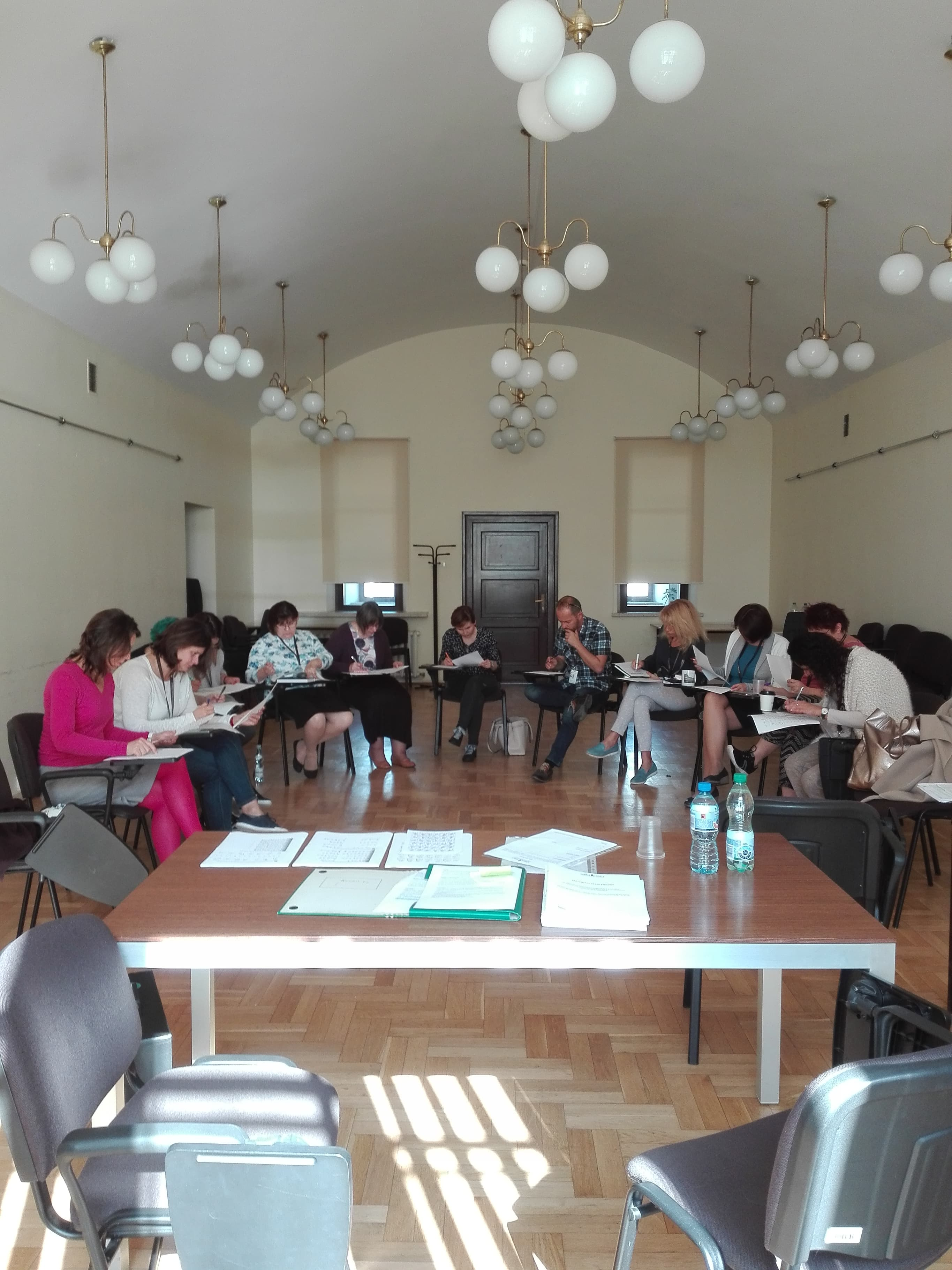 11 uczestników siedzi w okręgu robiąc notatki