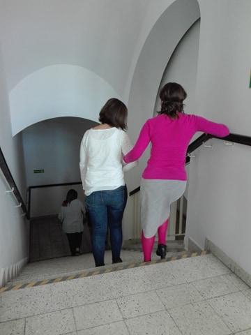 2 panie schodzą ze schodów, jedna prowadzi drugą