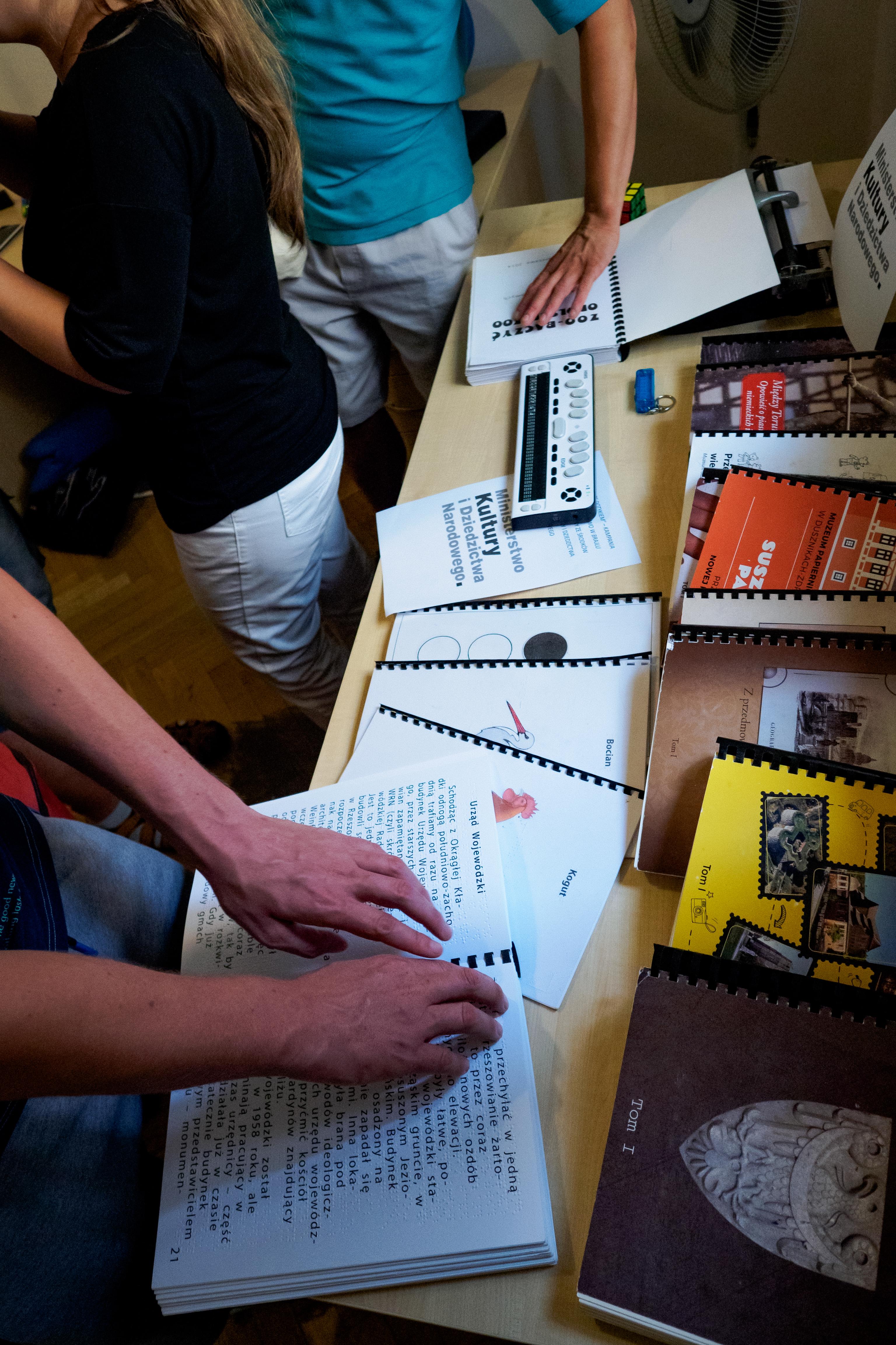 Dłonie dotykające brajlowskie publikacje.