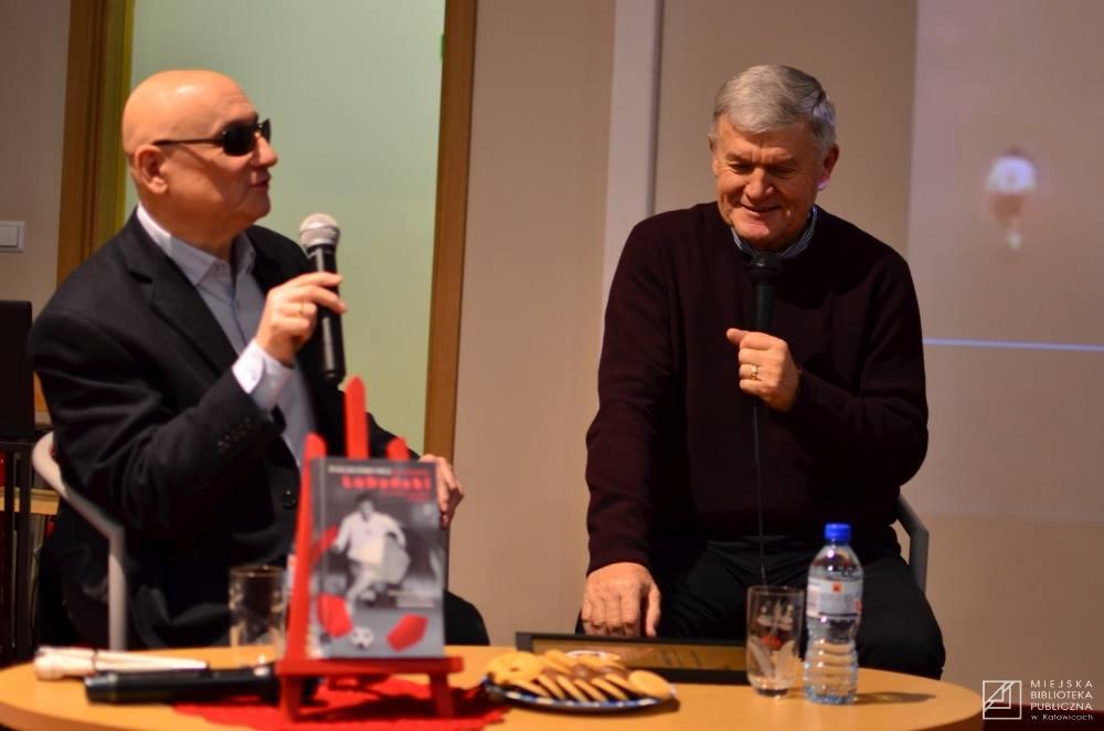 Pan Marek siedzi z mikrofonem po lewej stronie a po prawej stronie Lubański, na stoliku książka o Lubańskim