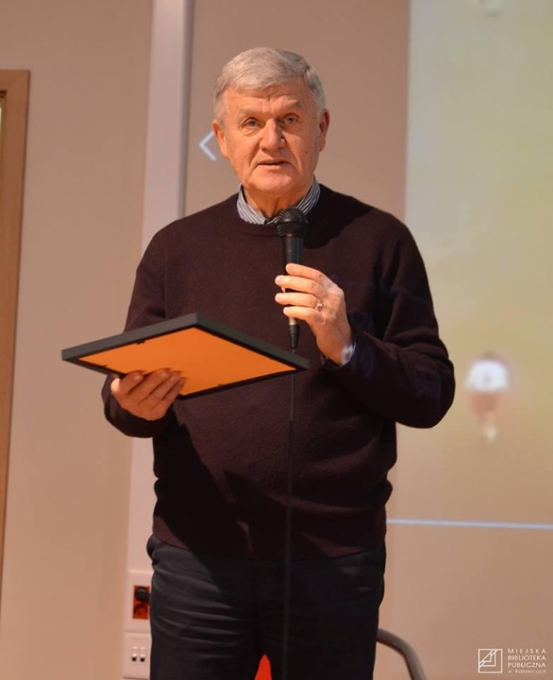 Pan Włodzimierz stoi z mikrofonem i dyplomem tyflograficznym IDOLA STULECIA