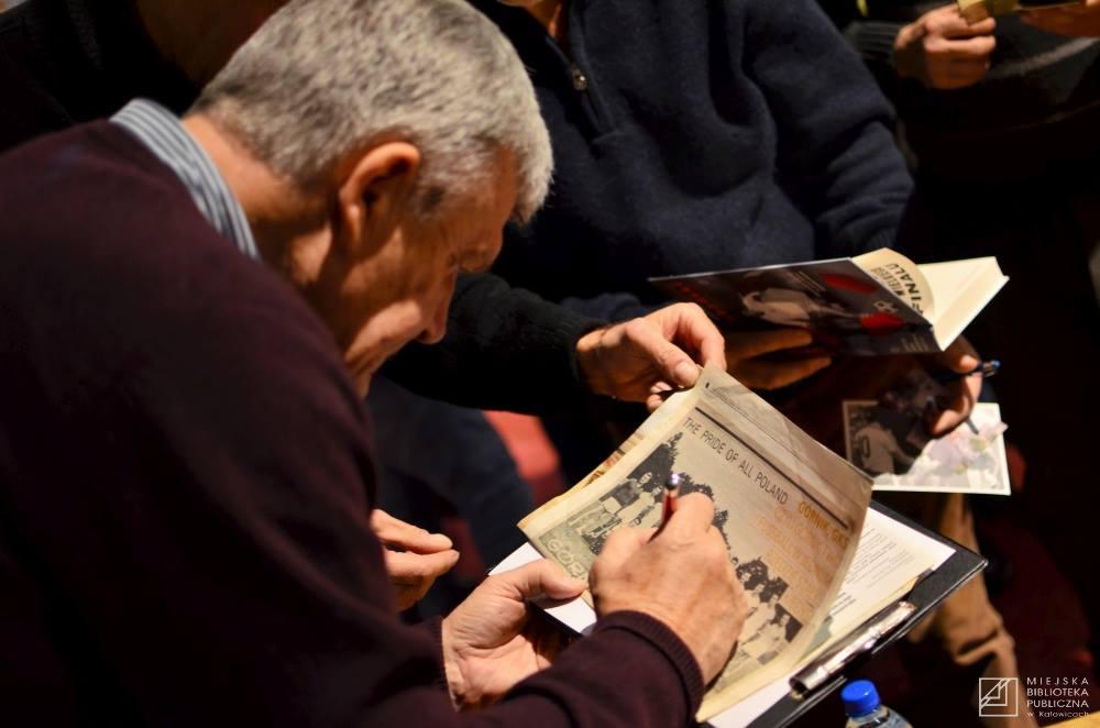 Pan Włodzimierz składa autograf na starej gazecie zawierającej artykuł o nim