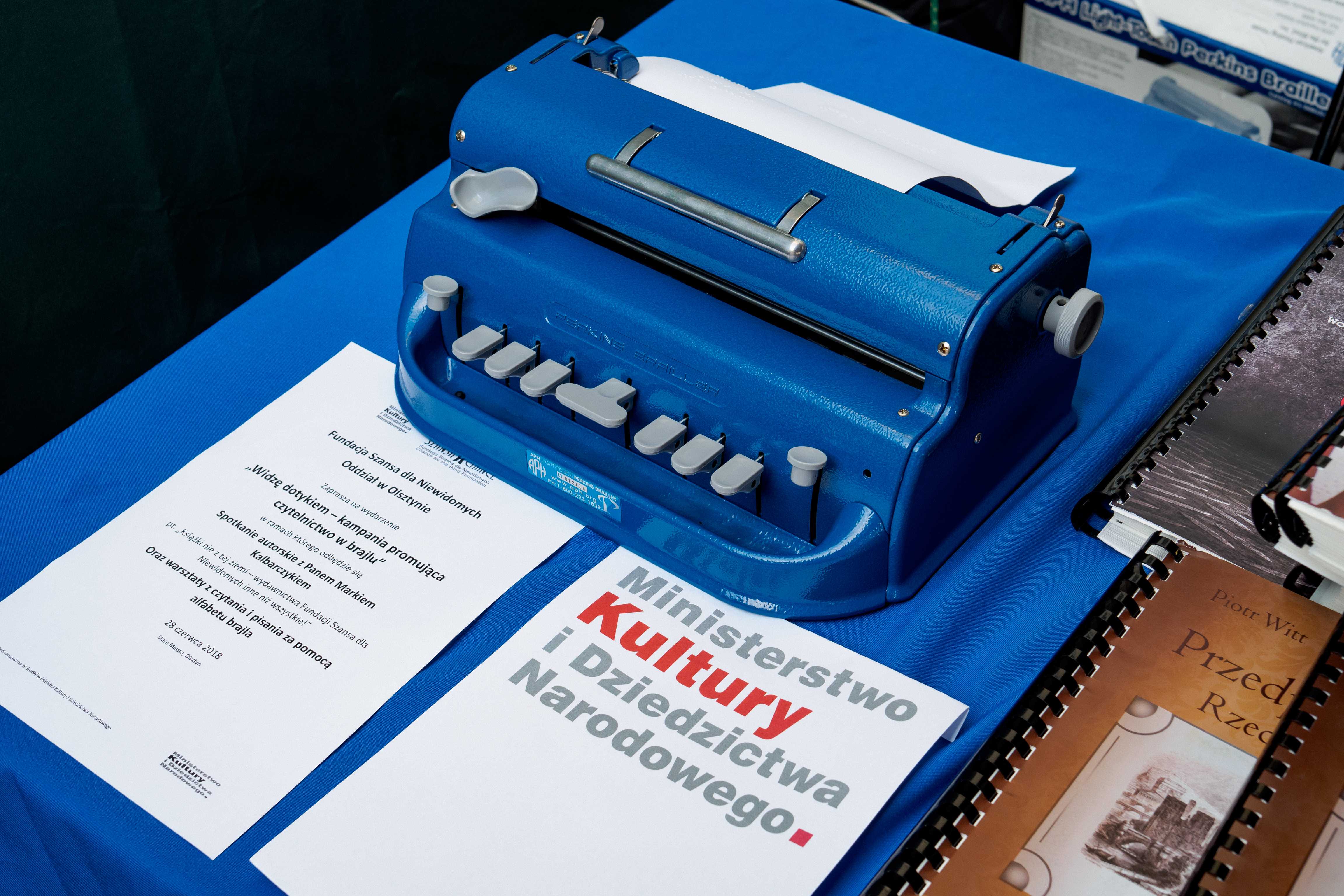 Maszyna brajlowska. Przed nią informacja o wydarzeniu i logo Ministerstwo Kultury i Dziedzictwa Narodowego.