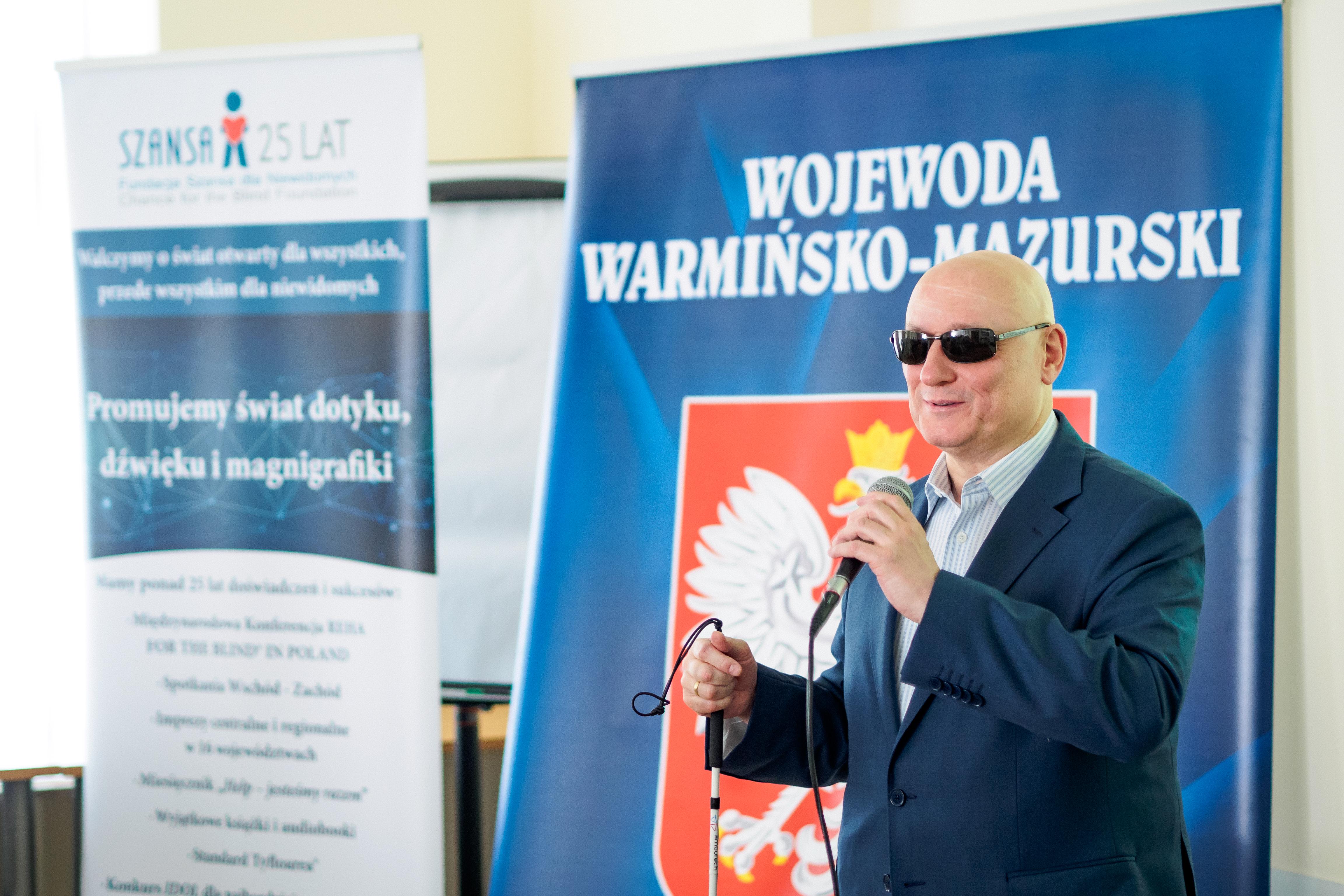 Pan Marek Kalbarczyk. W tle baner Konferencji REHA oraz Wojewody Warmińsko-Mazurskiego.