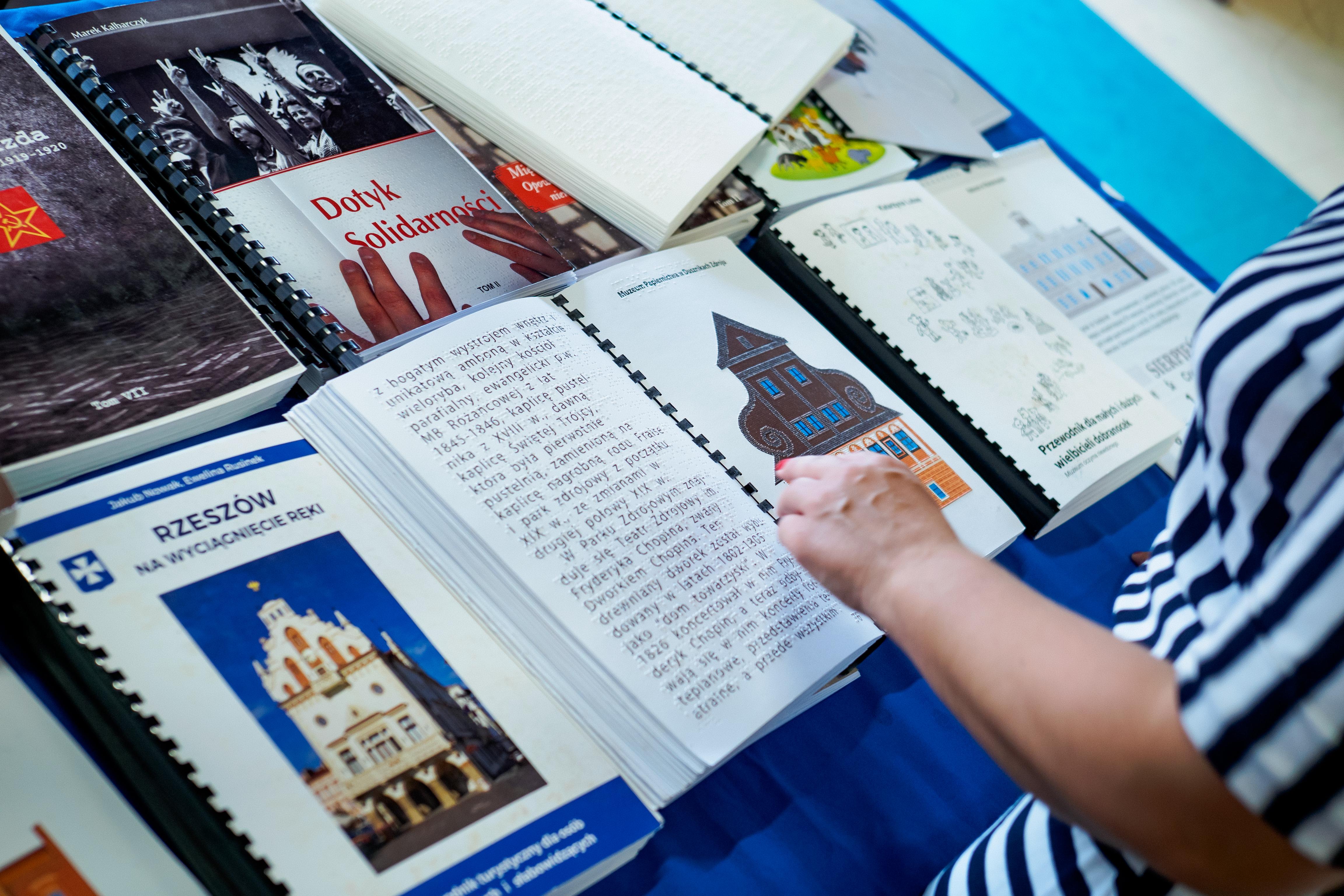 Otwarta jedna z publikacji brajlowskich. Ktoś kieruje palec w stronę książki.