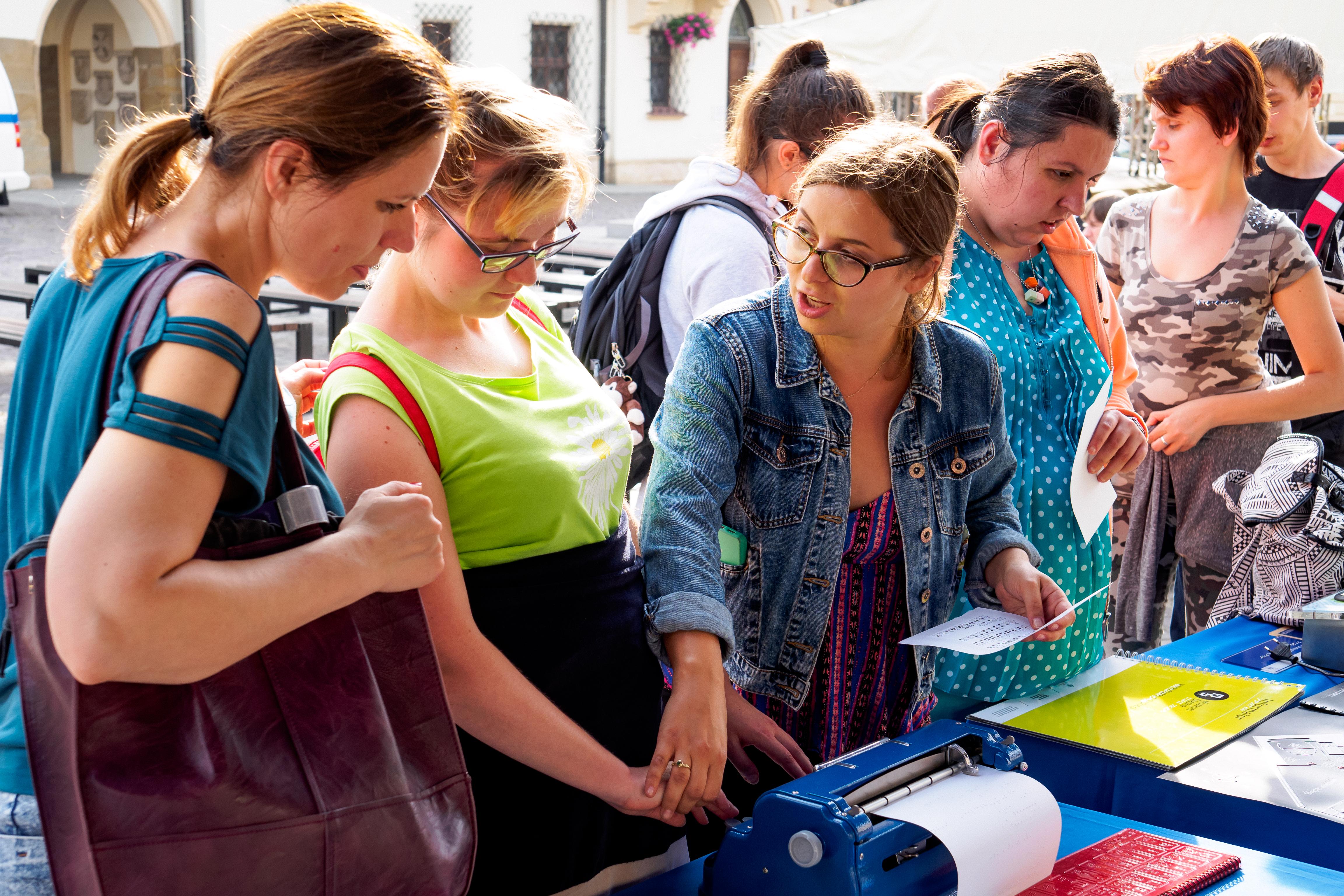 Piknik. 6 osób wokół stołu i kobieta pokazująca maszynę brajlowską.