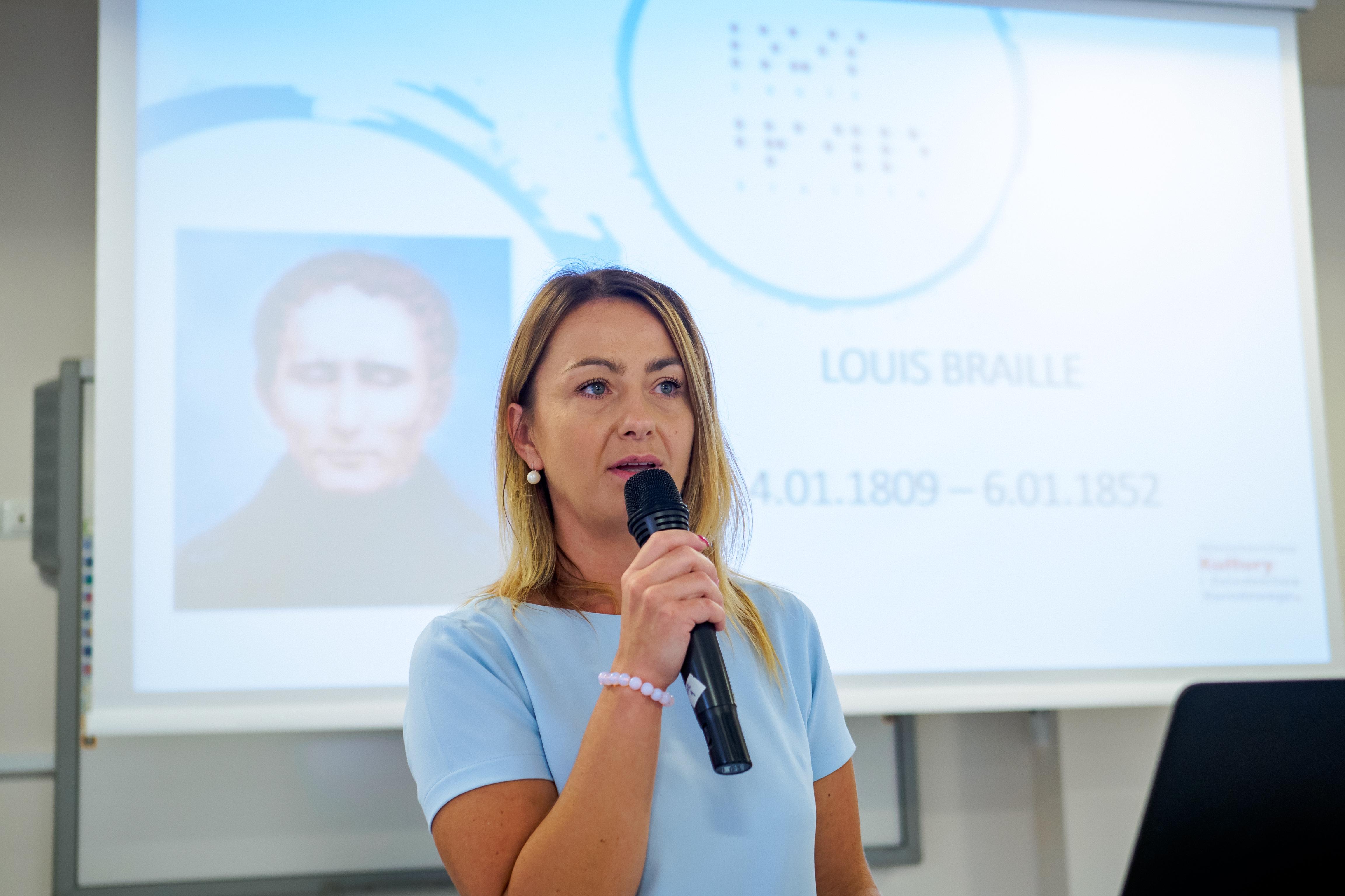 Kobieta z mikrofonem. W tle prezentacja dotycząca Louise Braille'a.