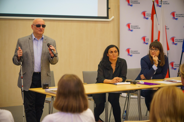 Pan Marek Kalbarczyk stoi z mikrofonem. Obok niego siedzą dwie kobiety.