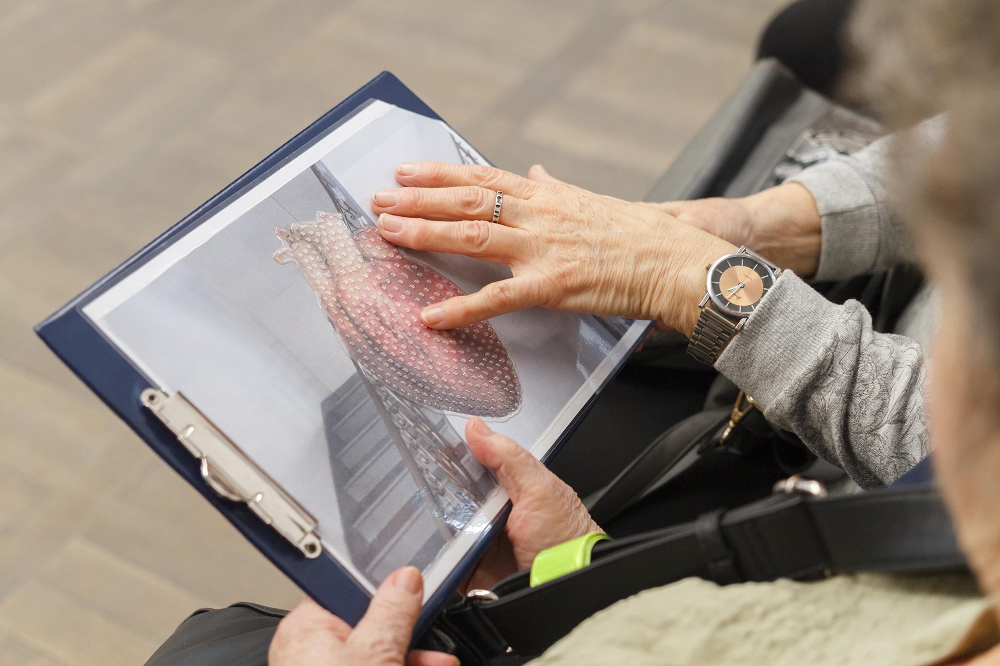 Wydrukowana podobizna rzeźby, wydrukowana na termoformowalnym papierze, wypukła, na zdjęciu ręka która jej dotyka