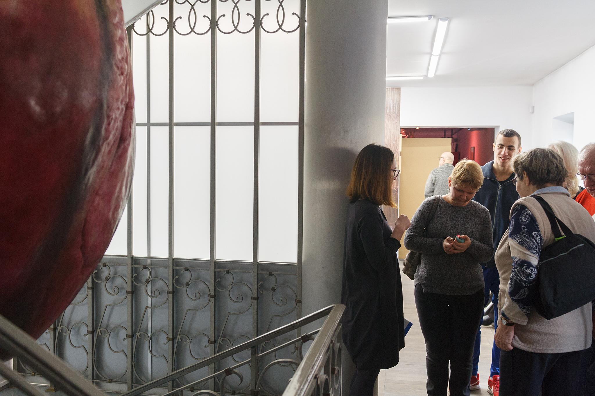 zdjęcie wykonane z takiej perspektywy, że z lewej strony widać rzeźbę serca a z prawej rozmawiających ludzi