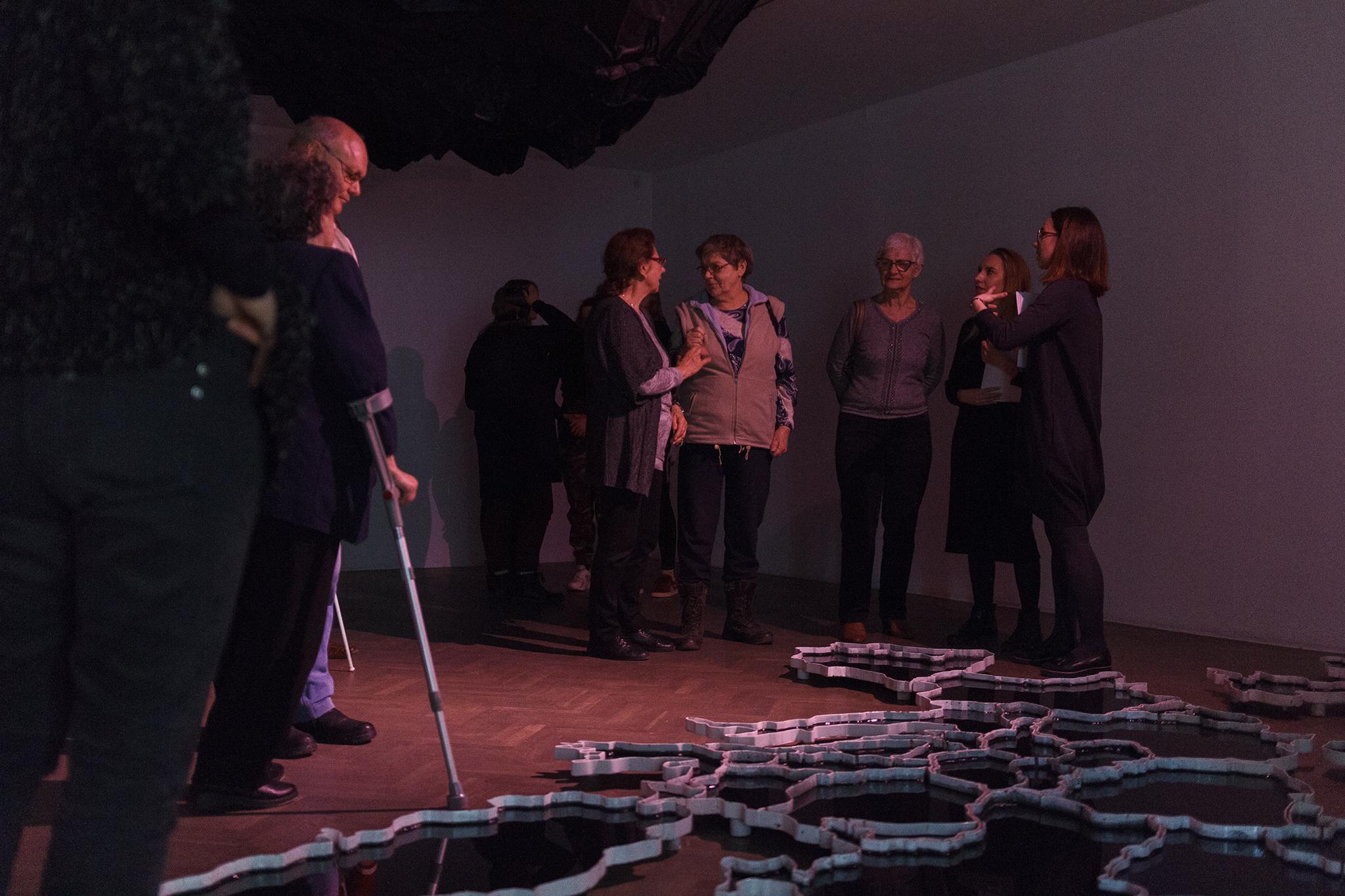 grupa 7 osób w ciemnym pomieszczeniu, przed nimi na ziemi leżą fragmenty w kształcie pilastru miodu tworzące kompozycję
