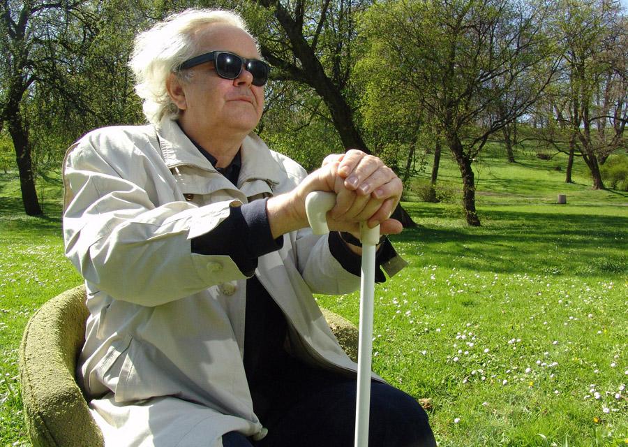 profesor Dłużniewski, siedzi na fotelu, w tle intensywnie zielona trawa, drzewa