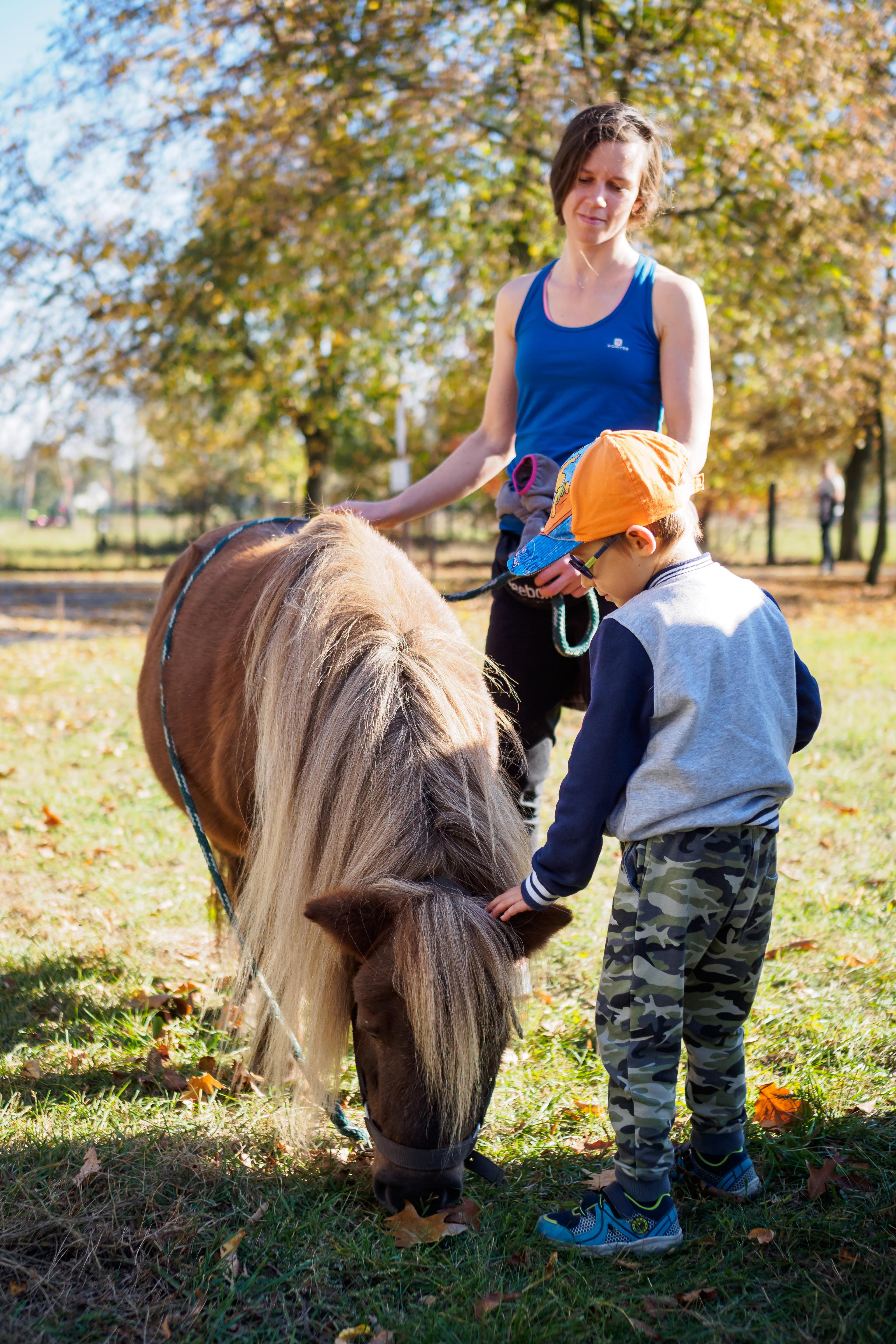 Zajęcia z hipoterapii. Instruktorka a obok niej chłopak głaszczący konia.