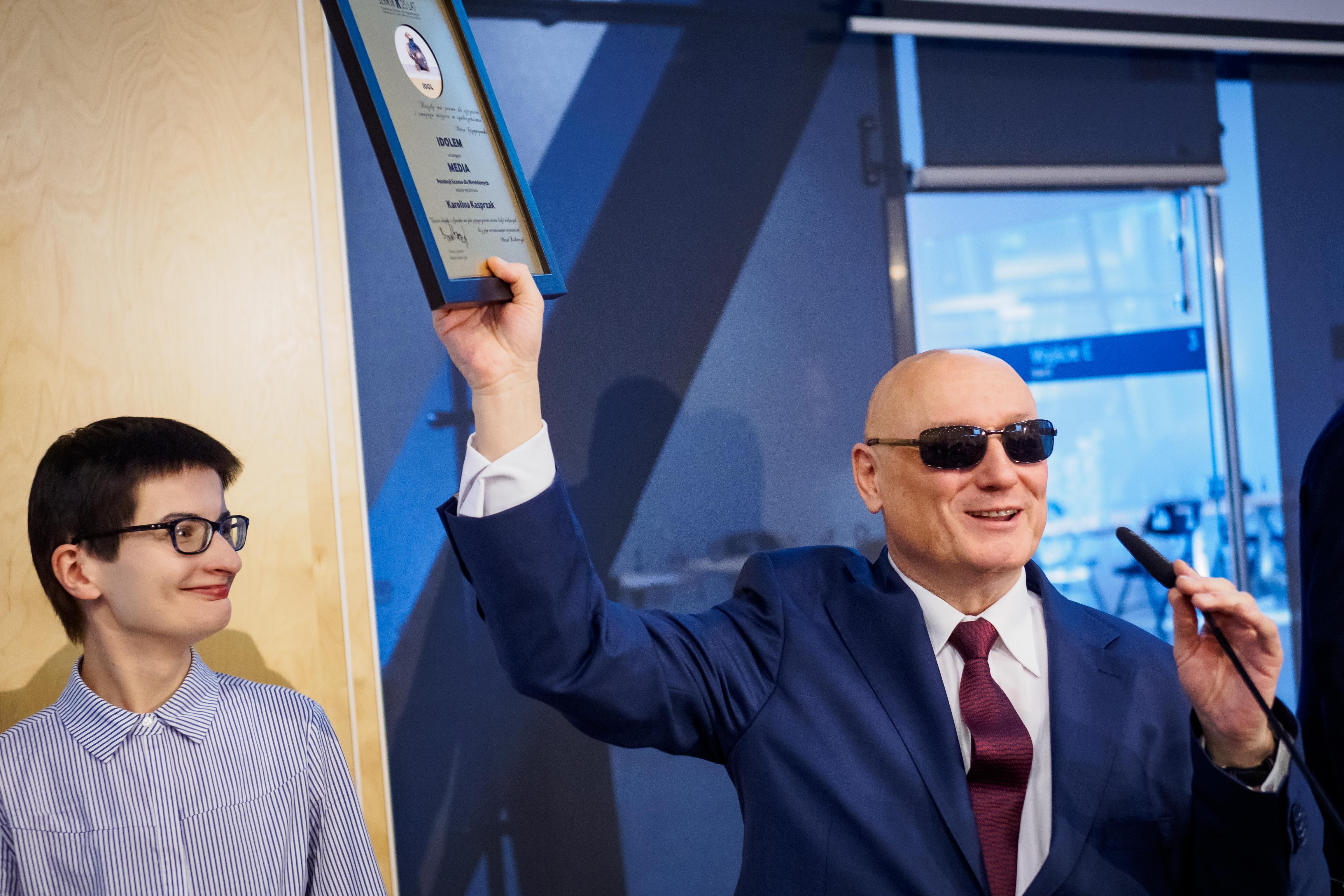 Prezes Marek Kalbarczyk wręcza nagrodę Idola w kategorii Media dla Karoliny Kasprzak unosząc dyplom tyflograficzny do góry.