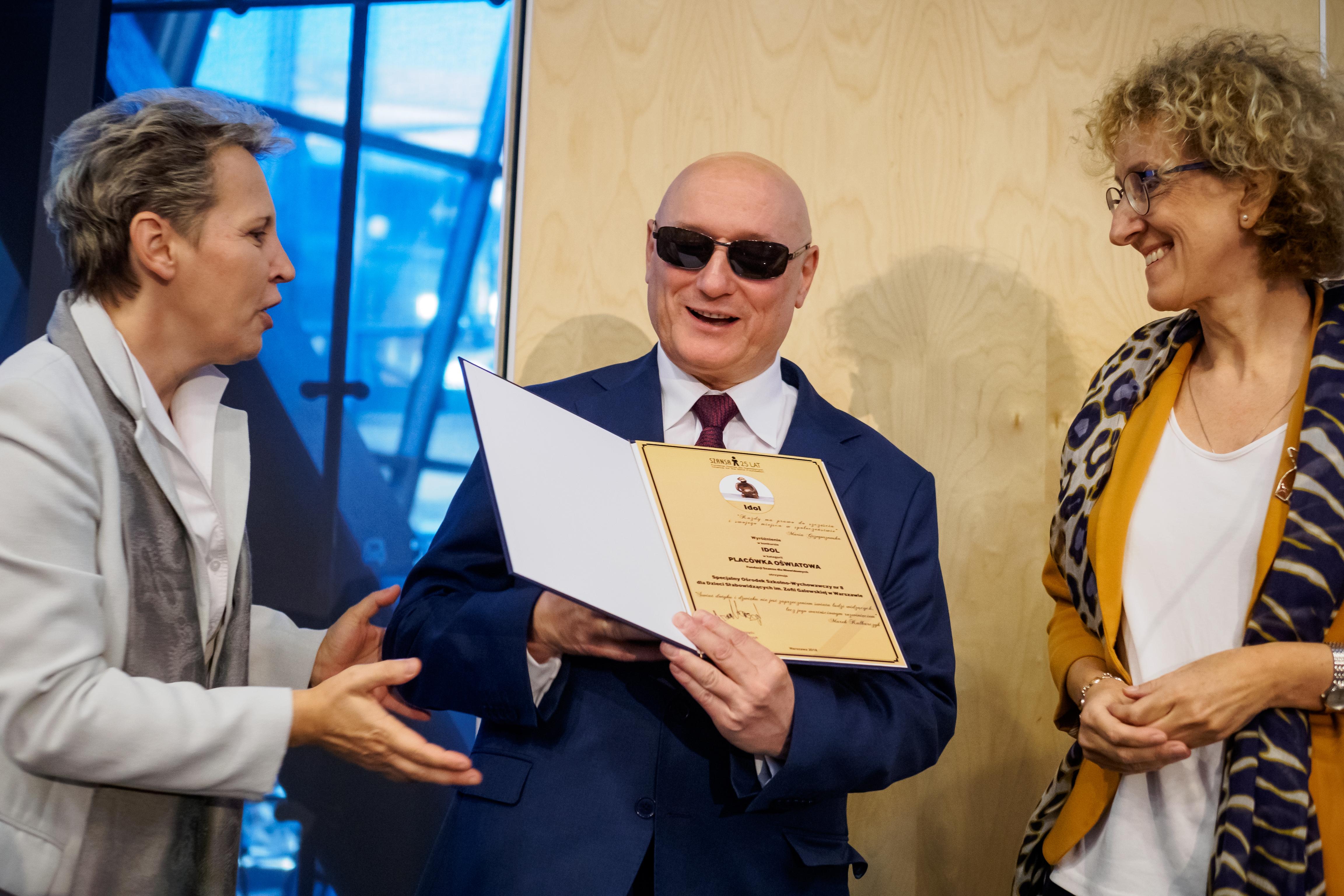Prezes Kalbarczyk z dyplomem i obok niego dwie przedstawicielki w kategorii IDOL PLACÓWKA OŚWIATOWA.
