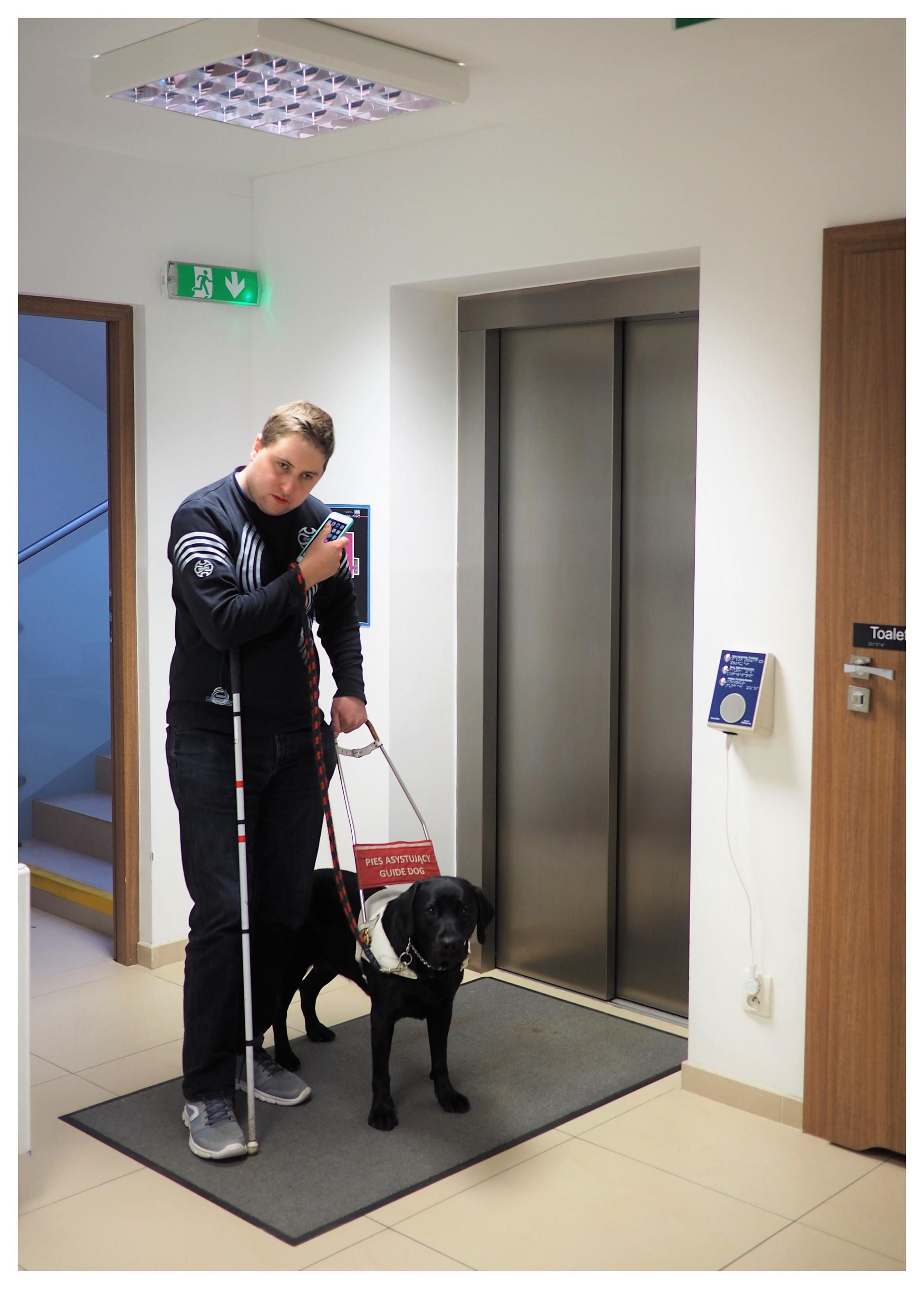mężczyzna z psem i laską, trzyma przy uchu telefon, za nim winda